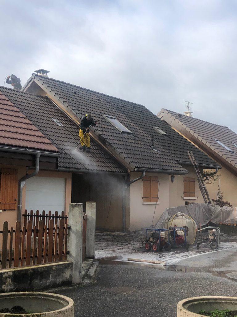Un de nos ouvrier en train de démousser une toiture chez un particulier